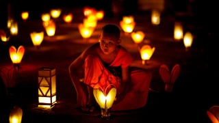 A young novice sets down a lantern in the temple