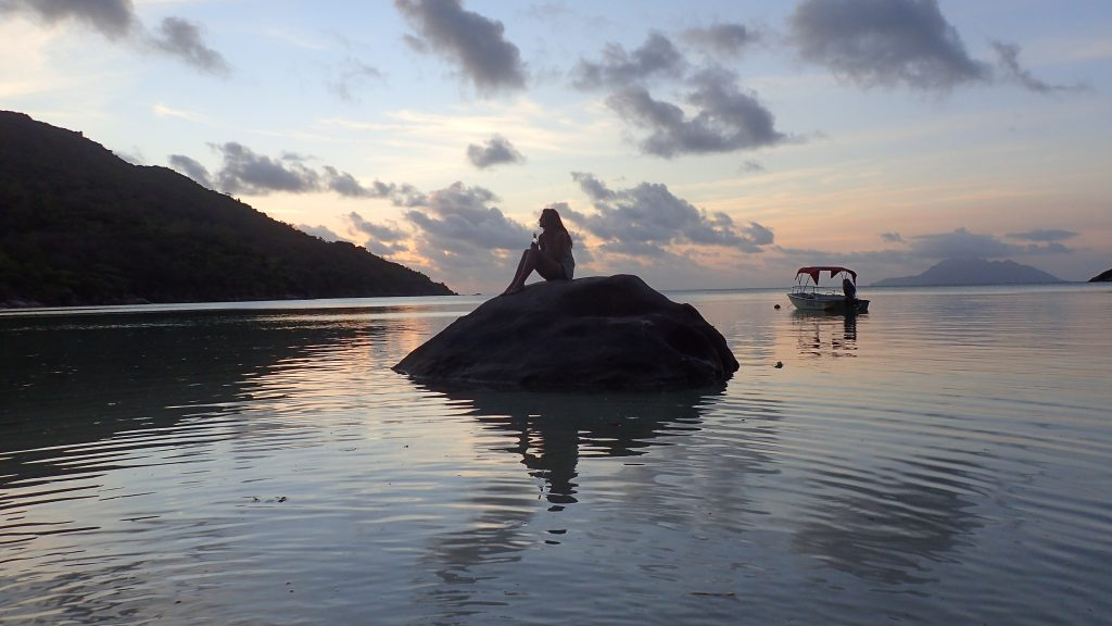 woman sitting on a rock in the ocean