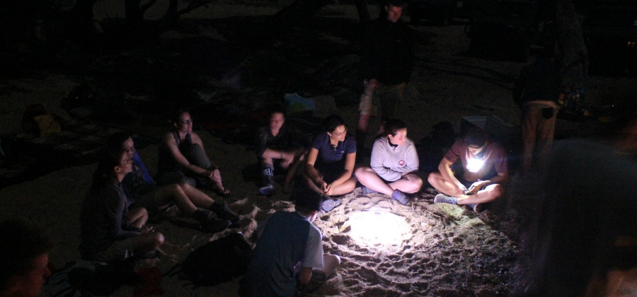 conservationists sitting around camp light