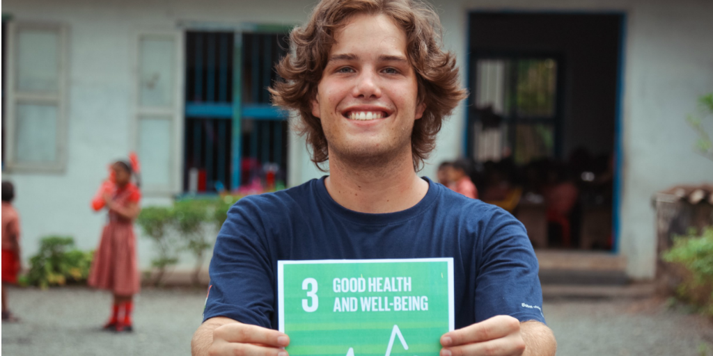 A GVI volunteer holding up the UN SDG related to public health.