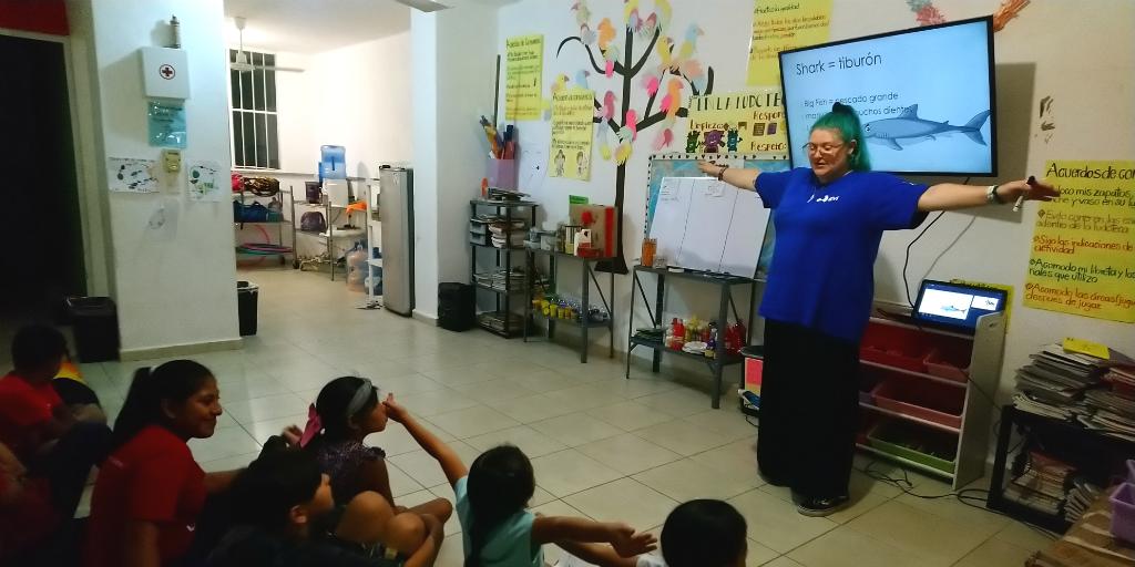 A volunteer teaching children about sharks.