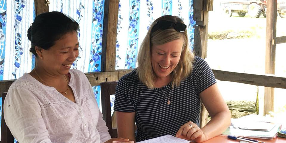 A GVI participants works on English language skills with a woman in Laos. This is one of many kinds of career break work abroad.