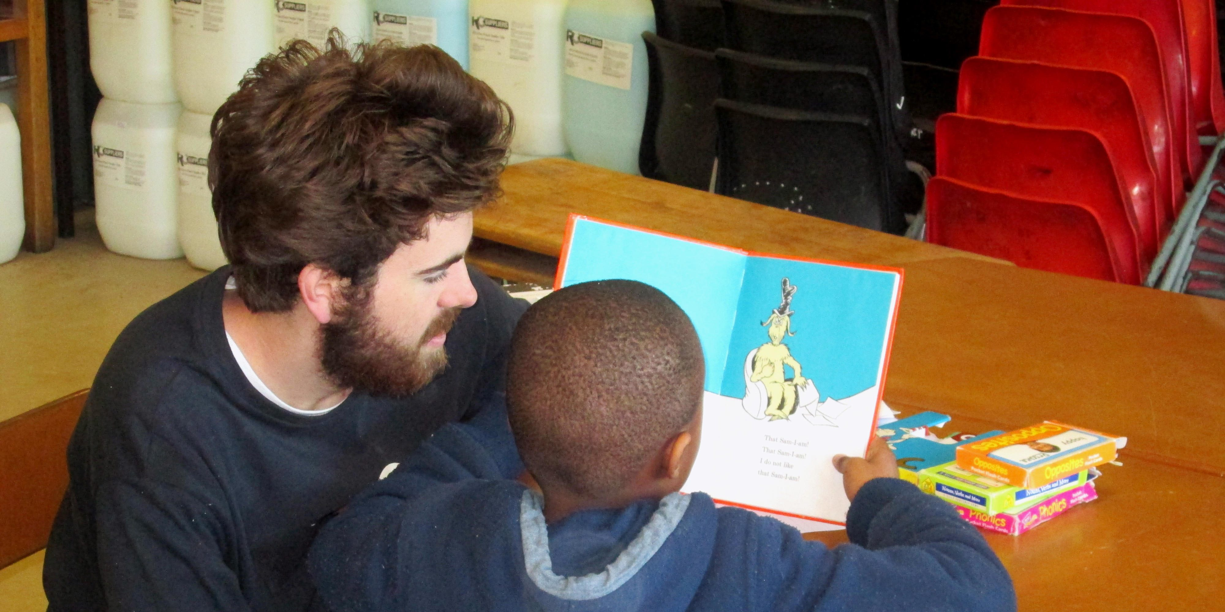 A GVI participant helps a learner with their reading while teaching English abroad.