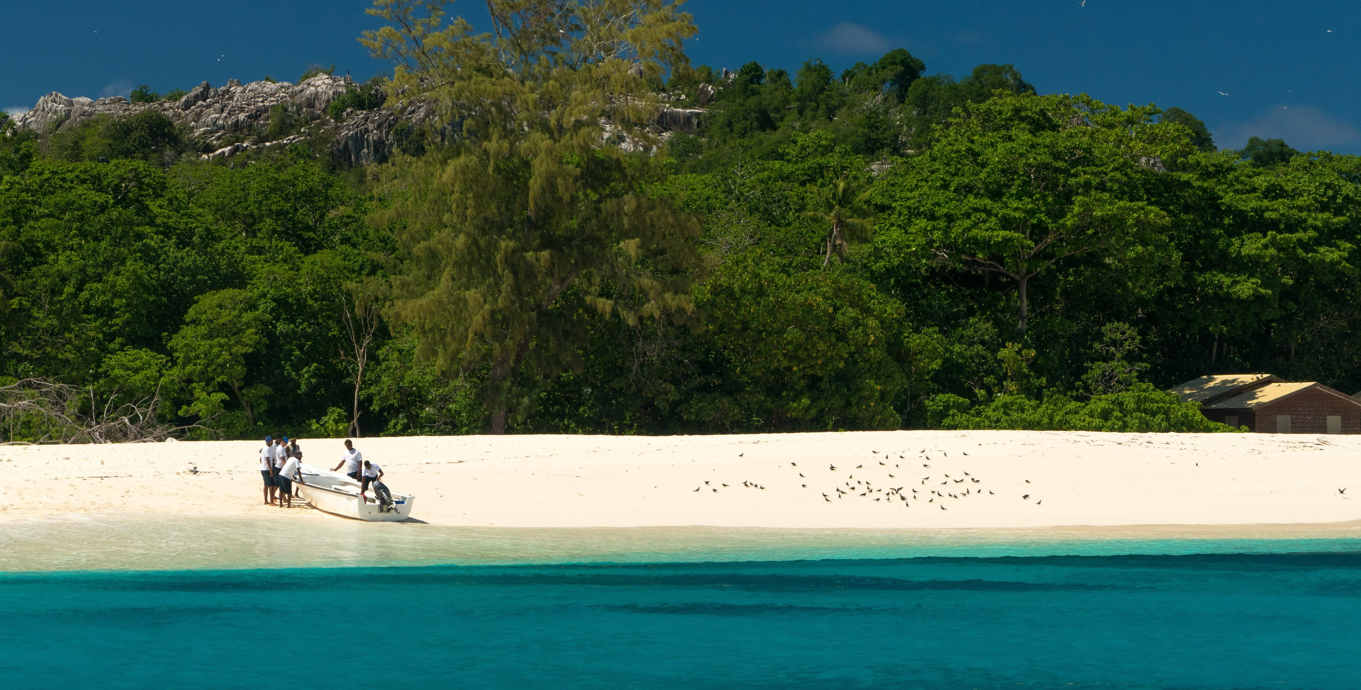 A small boat is pushed onto a beach on Bird Island in the Seychelles archipelago. This island is frequented by wildlife conservation officers and conservation volunteers.