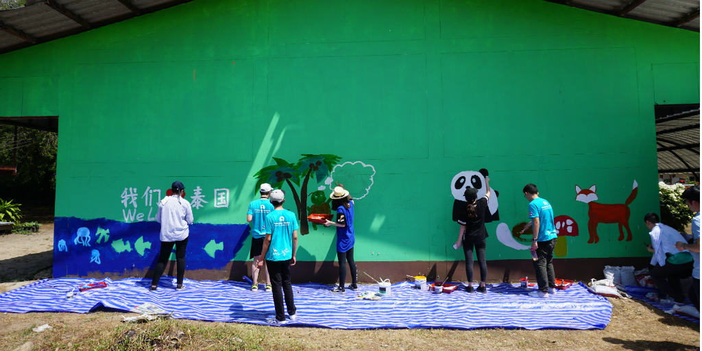 Members of a volunteer group abroad with GVI paint a mural on a wall in Thailand