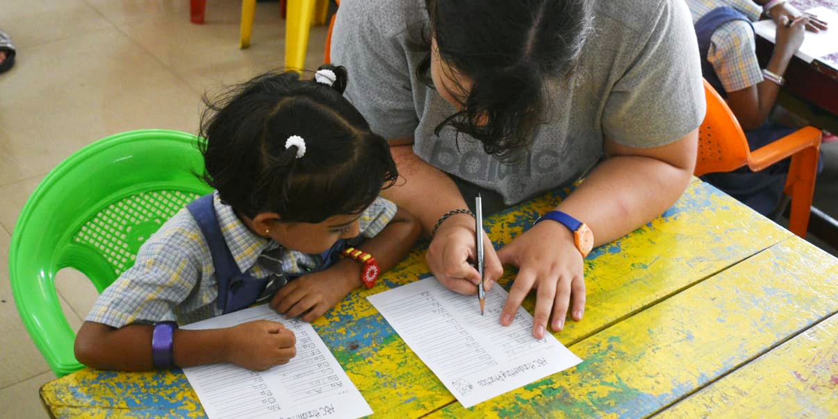 A GVI participant helps a learner complete a worksheet while volunteering in India.