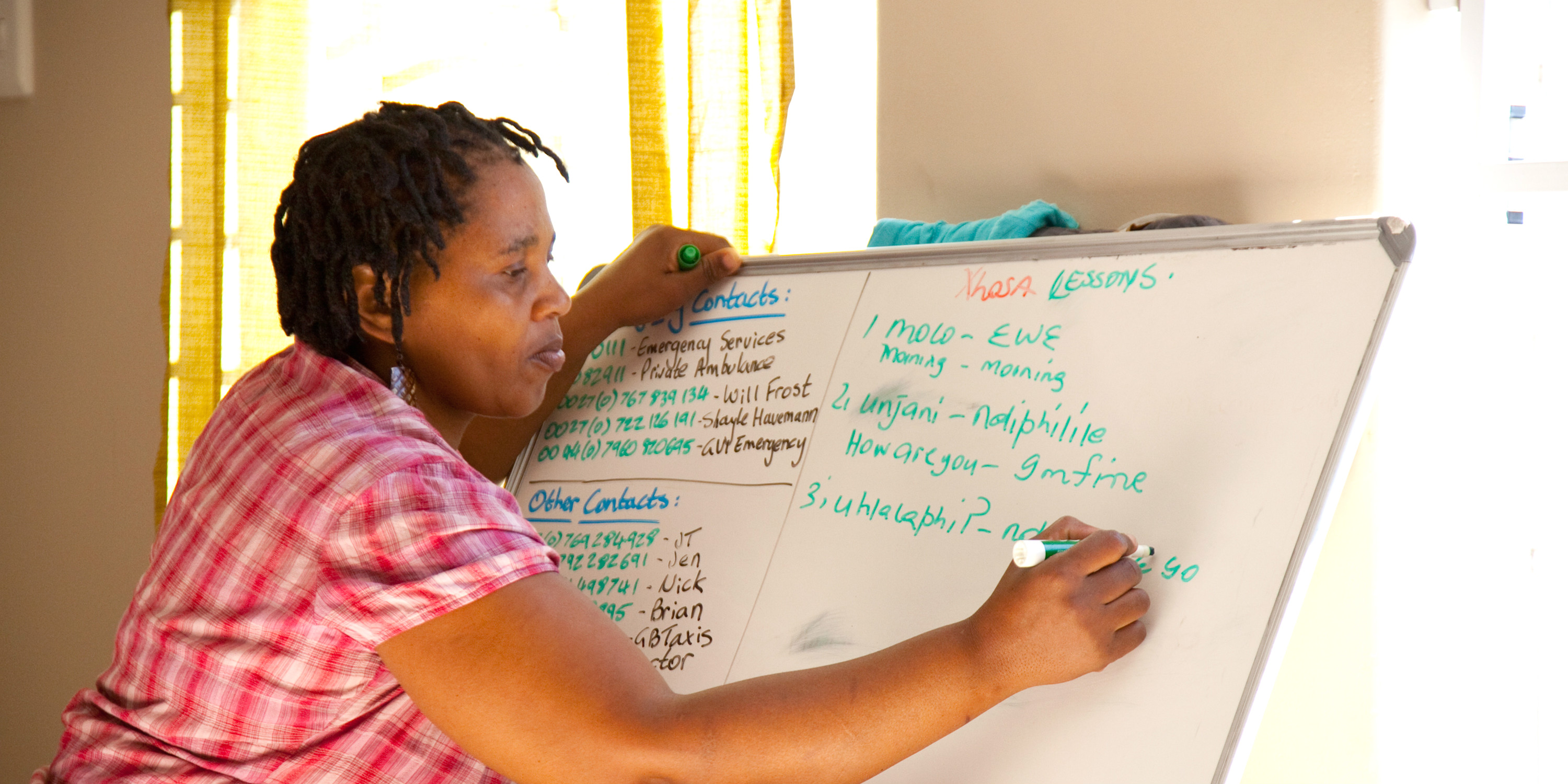 A women works on a language lesson with GVI, as part of a women's empowerment program.