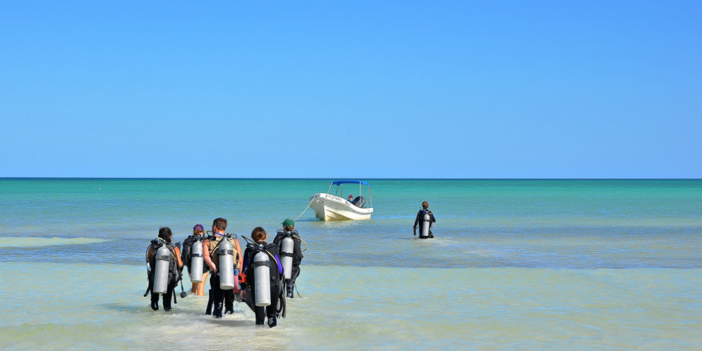 Participants on a research expedition heading out scuba diving.