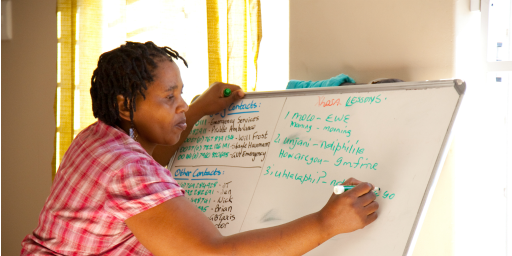 A local South African woman writes on a white board