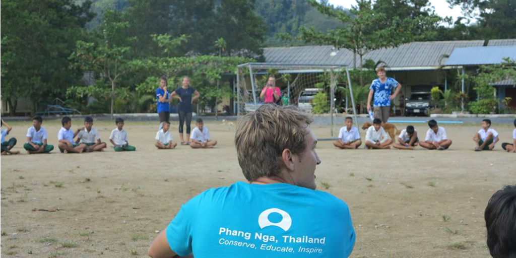 A GVI volunteer looking out over an outdoor class with children in Phang Nga, Thailand.
