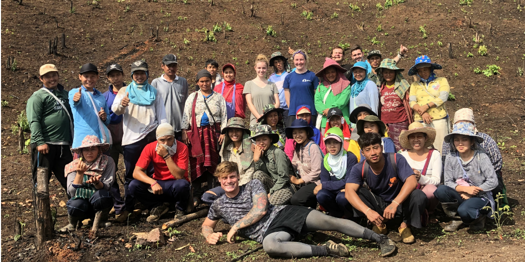 A group of volunteers with local people on a hillside.