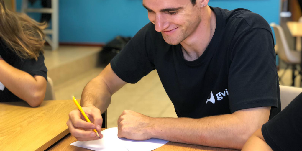 A volunteer sitting at a table and writing on a piece of paper.