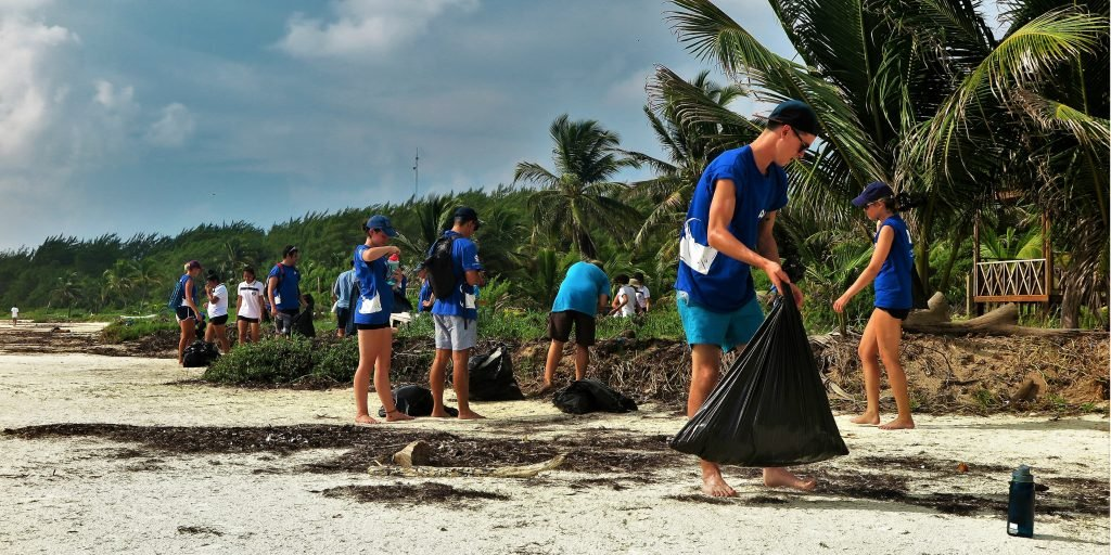 A large group of volunteers collecting litter during a beach clean up.