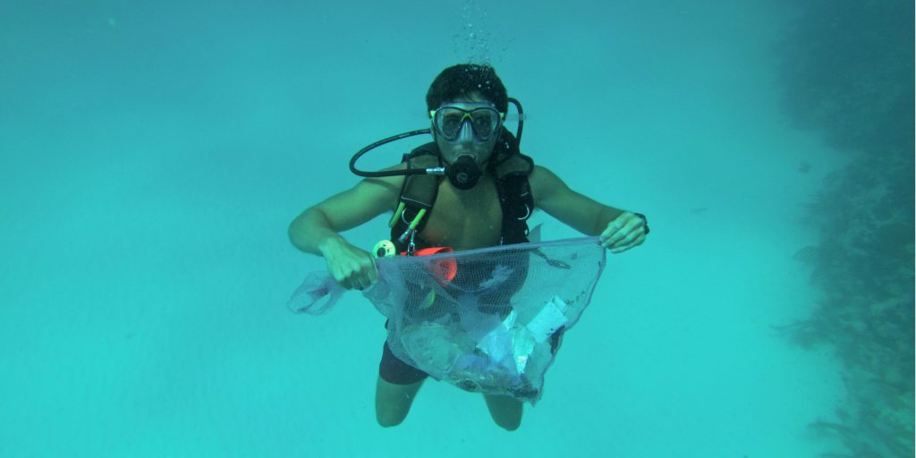 A diver showing off a mesh bag of litter collected from the ocean.