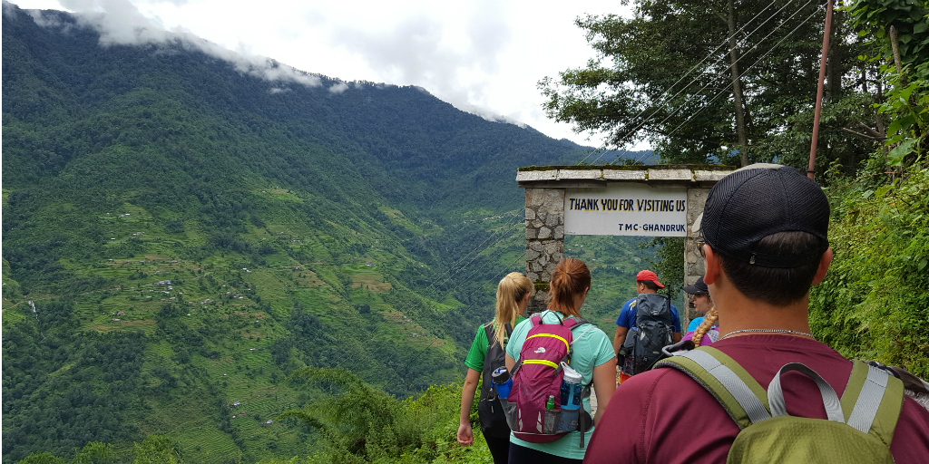 Teen hikers walking through an arch on a hiking trail in Nepal.