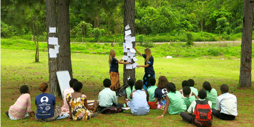 Two volunteers teaching a class outdoors.
