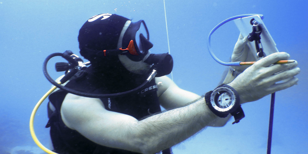 A diver recording findings on a notepad under water.