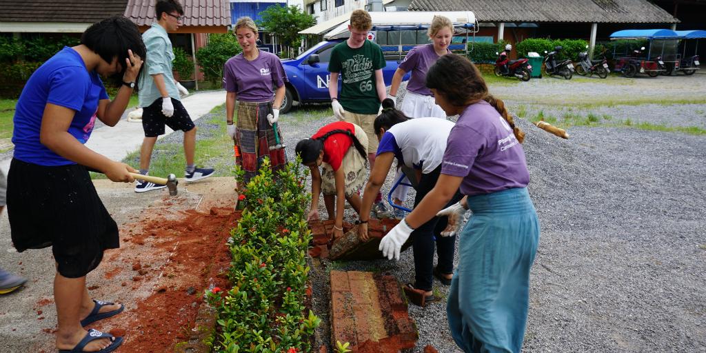 Teen volunteers working on community development garden installments in Thailand