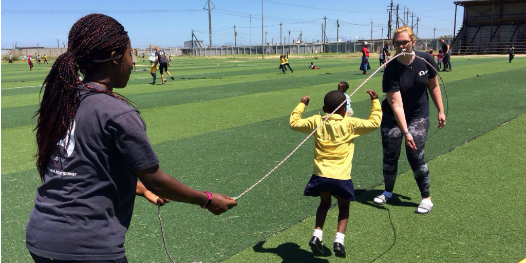 Volunteers swinging a skipping rope on a sports field while a child jumps the rope.