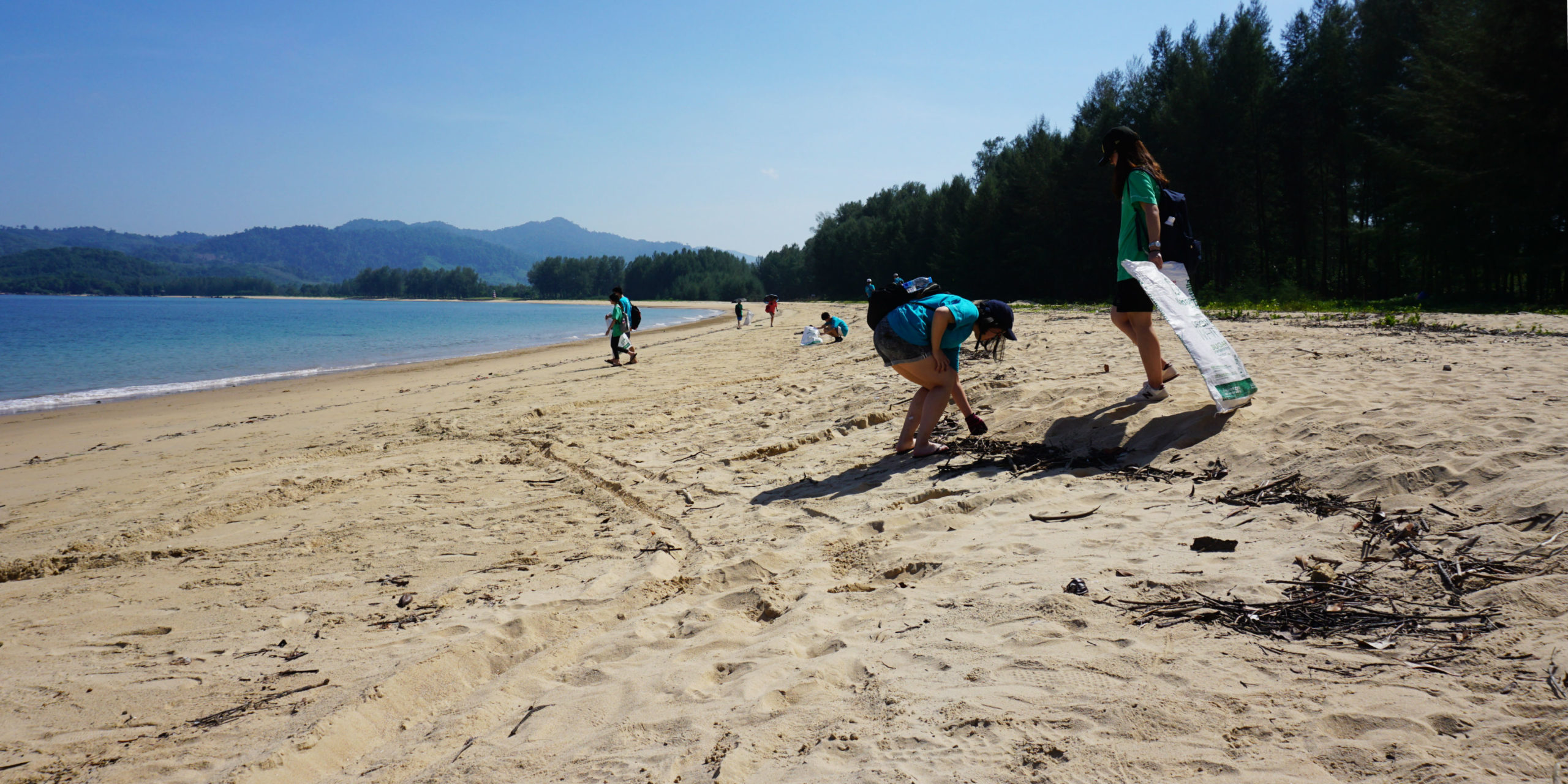A pair of participants collect litter from a beach while taking a gap year in Thailand.