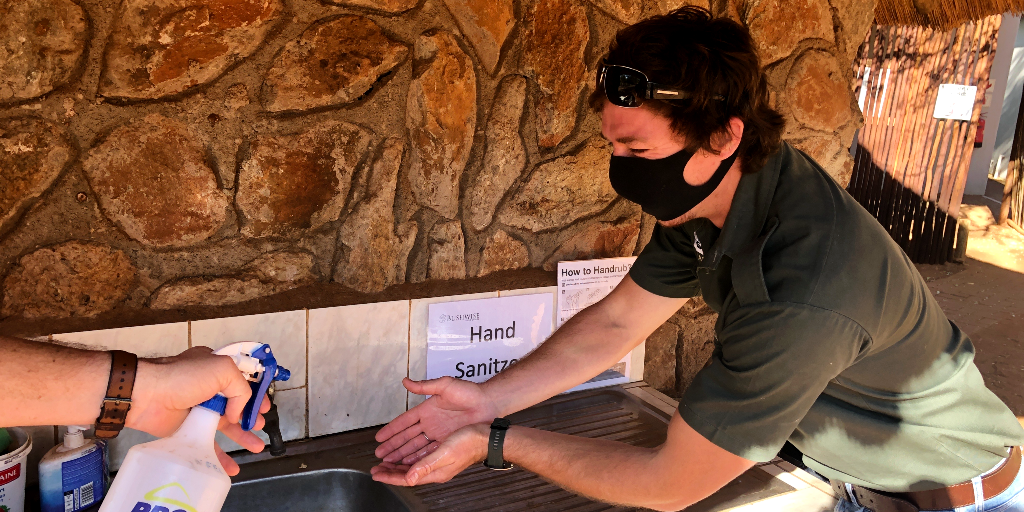 A man sanitises his hands to follow COVID-19 rules on a public health internship.