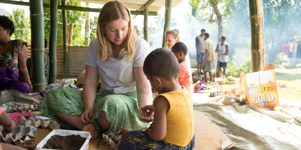 A GVI volunteers gives the child a seed to plant, to create a meaningful experience during her time abroad.