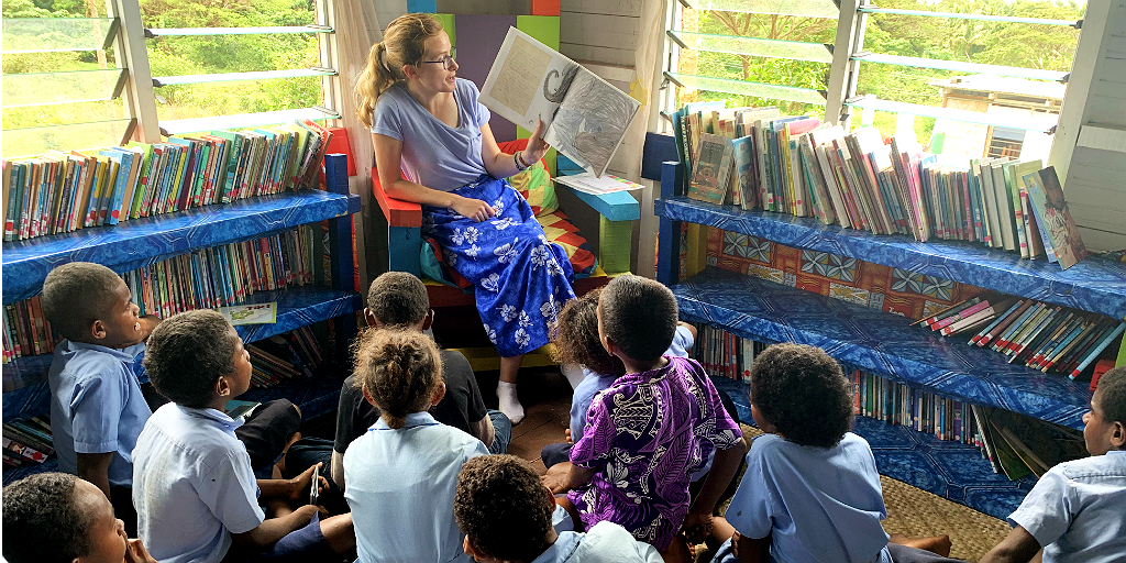 A woman reads a story to the children while being part of a language immersion program.