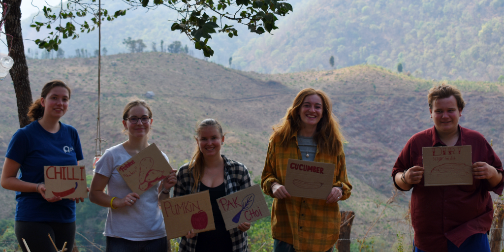 The environmental volunteers of GVI hold signs of what was planted in the community garden.