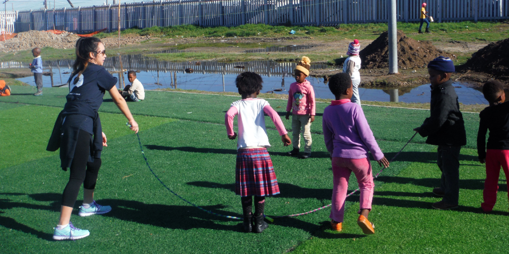 The GVI volunteer plays jump rope with the children.