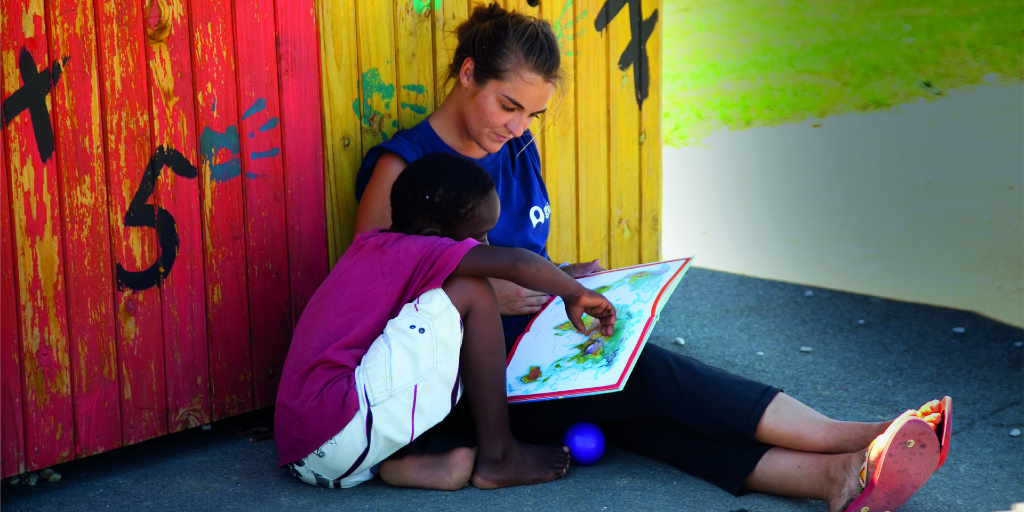A GVI volunteers helps a child read a book.