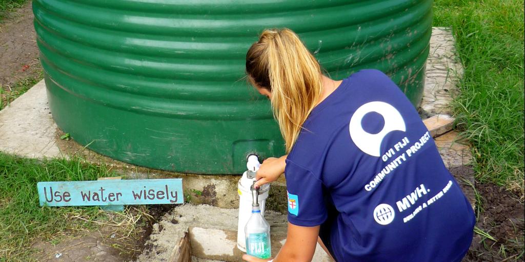 A GVI volunteer fills a water bottle from a water tank.